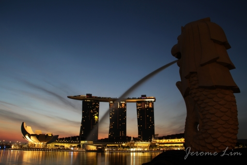 An icon of a developing and newly independent Singapore, the Merlion, stares at the icons of the new Singapore across a body of water that played an important role in Singapore's development.