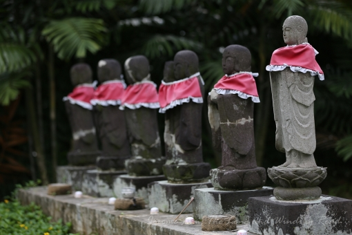 Dressed jizo statues at the entrance to the cemetery.
