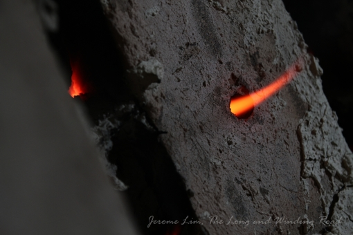 Flames seen passing through an opening hole (for inserting a temperature sensor) on a covered stoke hole.