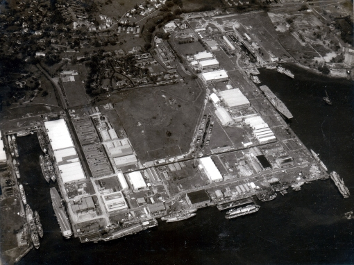 An aerial view of the Naval Dockyard in 1962 (Image: Horatio J. Kookaburra on Flickr). The former Stores Basin can be seen on the lower left of the photo and the King George VI dock can be seen close to the top right. Three floating docks are today tied up along a finger pier constructed off the 850 metre northwall. The northwall is seen running along the lower edge of the photo.