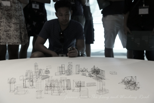 A participant takes a closer look at 'Fragile Structures' - the work of Frayn Yong which involves wireframe like models of structures found around Marina Bay made of mechanical pencil lead.