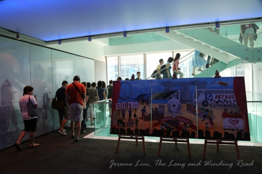 Participants heading to the 18th Floor - the trading floor of Deutsche Bank where photography is not permitted. The Deutsche Bank mural painted entirely by the bank's staff is seen in the foreground.