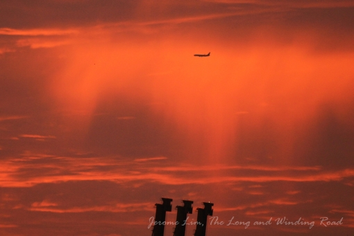 A plane is seen over the container cranes against the orangey sky at 7.14 am.