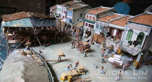 A diorama of Telok Ayer Street in the early days of modern Singapore showing where the shoreline was. The low building across from the Chinese Opera stage is the Fuk Tak Chi Temple.
