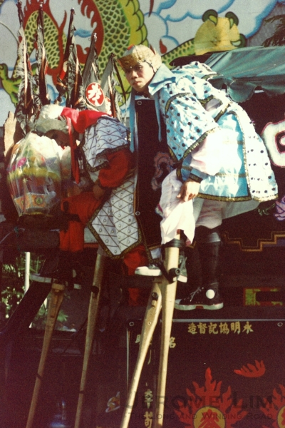Stilt-walkers resting along the Orchard Road route in 1985.
