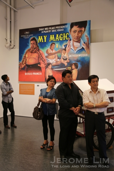 Former movie poster painter Mr Ang Hao Sai. Behind him is a hand-painted movie poster made for his 2008 film, My Magic.