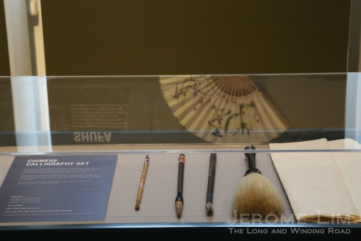 A reflection of a fan with Chinese calligraphy with a showcase of showing the tools of the trade.
