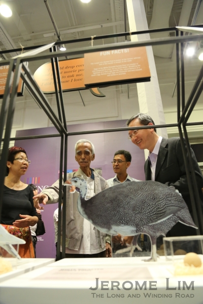 Mr Ho Seng Choon, of Lian Wah Hang Quail and Poultry Farm, one of the six tradesmen featured, speaking to Mr Sam Tan, Senior Parliamentary Secretary, Ministry of Culture, Community and Youth at the opening of the exhibition.