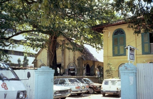The church building when it was used as a motor workshop and the Tai Loke Hotel next to it, 1987 (source: http://a2o.nas.sg/picas/)