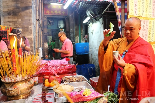 A monk blessing offerings at the Kuan Tai Temple.