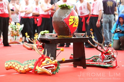 A jar of wine and wooden dragons for the ritual dance before the participants set off.