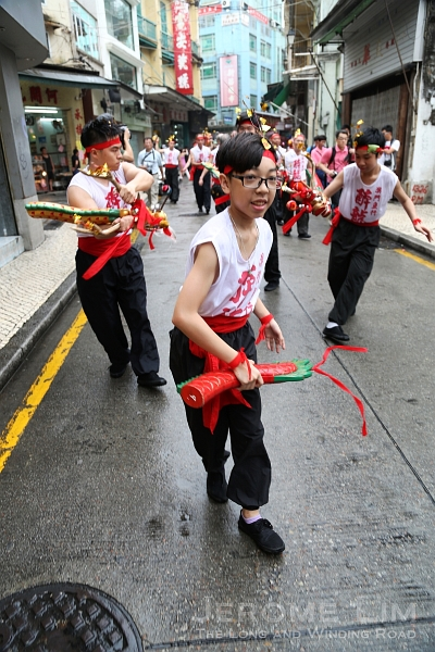 The procession of participants in martial art inspired dance makes its way through the narrow streets off Senado Square.