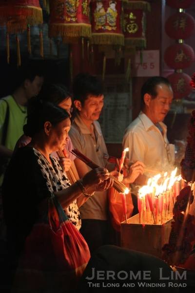 Devotees offering candles at the Pulau Ubin Tua Pek Kong Temple. The temples celebrates two festivals in a big way.