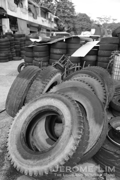 Truck tyres dominate the scene in front of the row of shophouses.