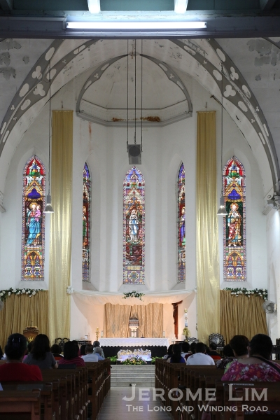 A view towards the sanctuary behind which five long stained panels can be be seen.