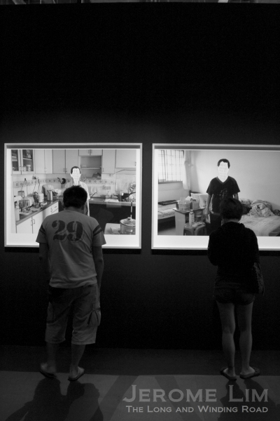 """A couple viewing a photography exhibit at """"Being Together: Family & Portraits - Photographing with John Clang""""."""