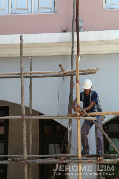 A scaffolding worker lashing the wooden poles.