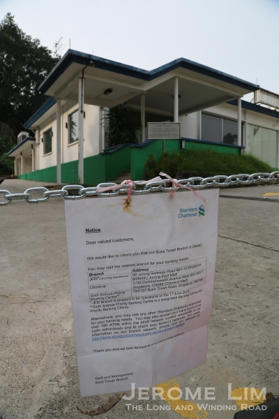 The recently closed Chartered Bank branch building with a notice of its closure.