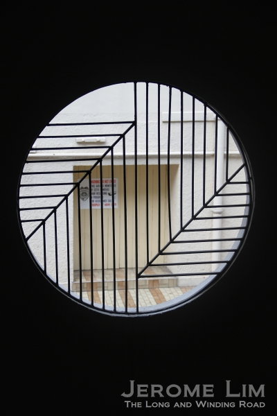 A view through a grilled opening of a staircase.