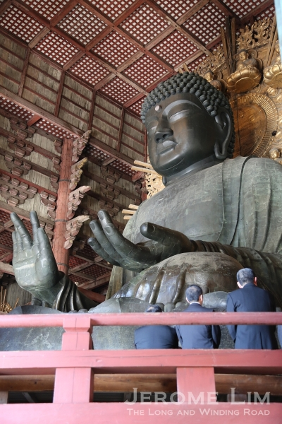 The scale of the giant Buddha can be seen against several suited businessmen attending a ceremony being conducted on a platform below it.