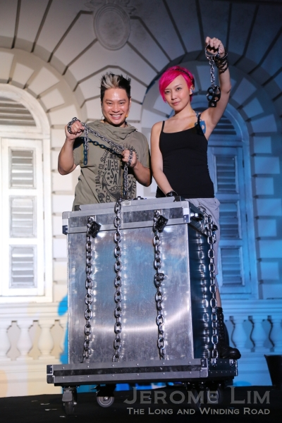 J C Sum and Magic Babe Ning with the locked and chained steel vault filled with water which she will attempted to escape from whilst shackled at the neck, wrists and waist.