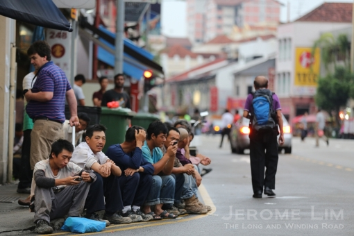 Migrant workers lining the Geylang kerbside  - a common sight in first hour of daylight.