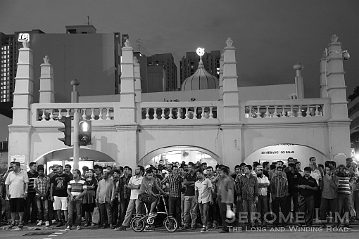 The gatehouse which has been put up for conservation, seen with the crowd after sunset prayers.