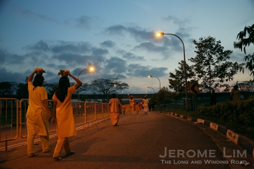 A walk into the light. Devotees carrying milk pots along the procession route at sunrise.