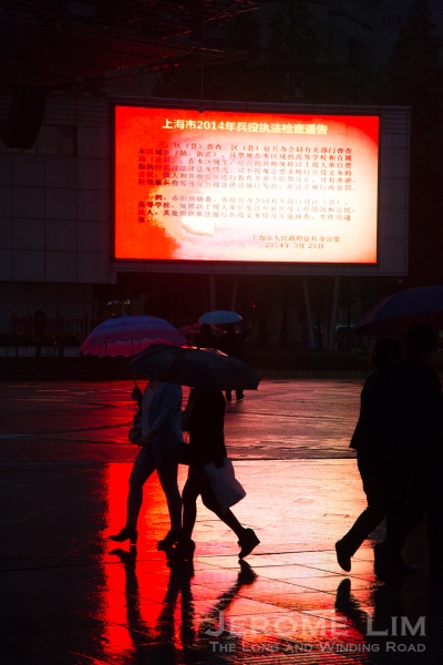 The neon coloured glow of Century Square  along Nanjing Road in the rain.