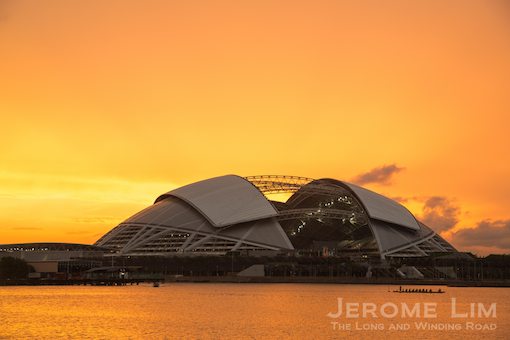 The new stadium with the silhouette of a dragon boat team in the Kallang Basin seen at sunrise.