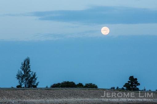 The super moon seen setting over Pulau Semakau.