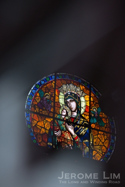 The circular stained glass panel seen through the closed gates of the church.