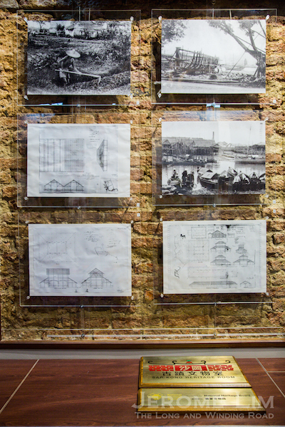 Among the exhibits is a set of historical photos and building plans that is set against part of a wall that has its plaster removed to reveal its original brickwork.