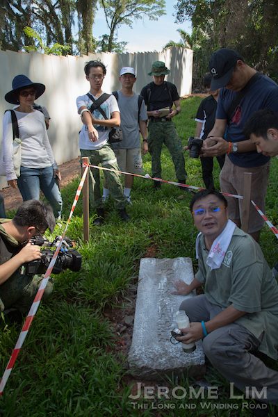 Raymond Goh showing how he uses flour to bring out the faint inscriptions on the third headstone.