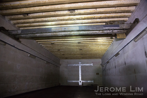 The storage area where  corrugated ceiling reinforcements can be seen along with a gantry hoist.