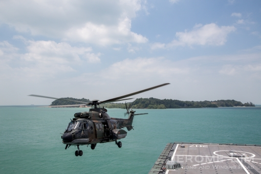 A Super Puma taking off at the Raffles Reserved Anchorage. Pulau Senang can be seen in the background.