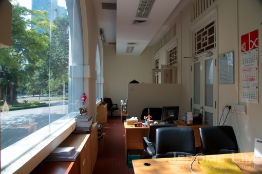 Beautifully bright office space created by closing the arches along the corridor of the smaller building with glass.