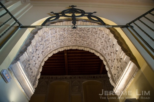 The 16th century grille and the arch decorated with Mudéjar plasterwork at the entrance to the El Oidor chapel.
