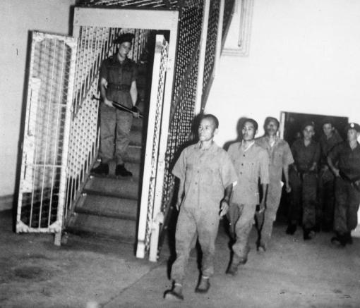 The caged passageway seen with indicted Japanese soldiers being tried for war crimes being led to the courtroom from the holding cells (source: Imperial War Museums © IWM (IND 4999).