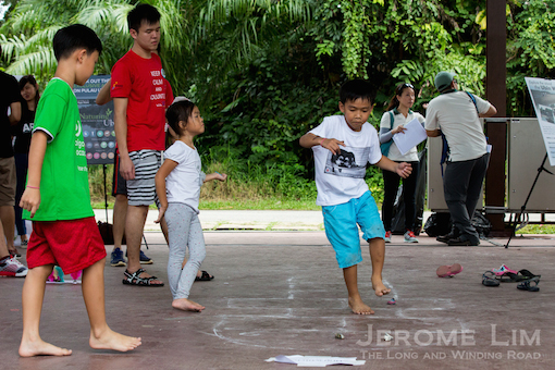 A boy playing a traditional game hopscotch.