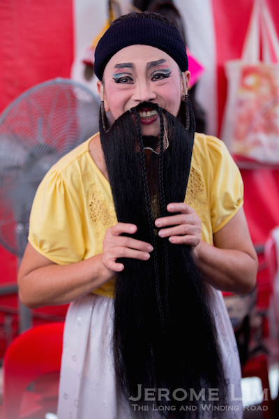 An female performer wearing a beard. While in the past only men could perform in an opera, there are more female performers these days and they would often be cast in male roles.