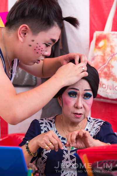 Performers now help each other with preparations. The blue make-up around the eyes is characteristic of Hokkien opera.