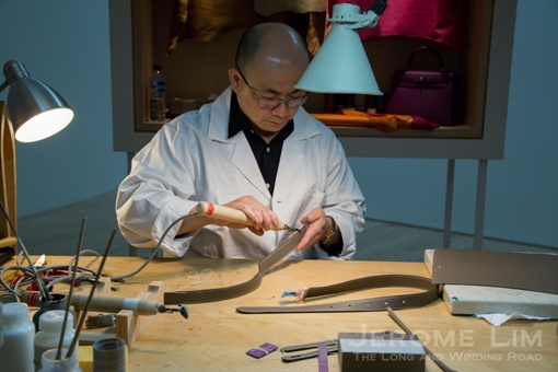An artisan from Hermès' Paris workshop at work at the ArtScience Museum.