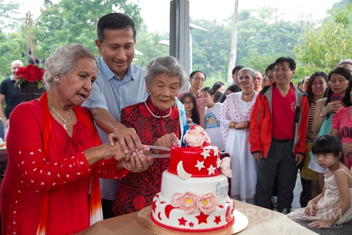 Two of the estate's oldest residents at the launch event cutting a cake with Dr Vivian Balakrishnan, Minister for Foreign Affairs.
