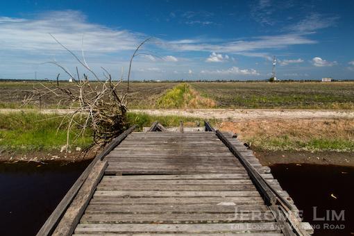 A wooden bridge over an irrigation canal.