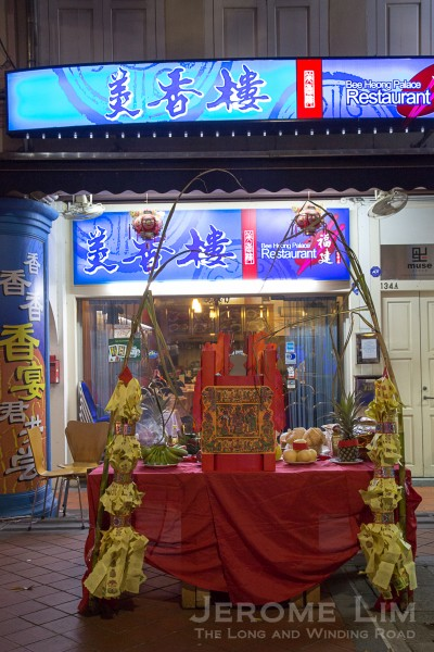 A table of offerings together with two stalks of sugarcane, placed at the front of a business. Similar tables are also seen outside the homes of Hokkien Taoist families.