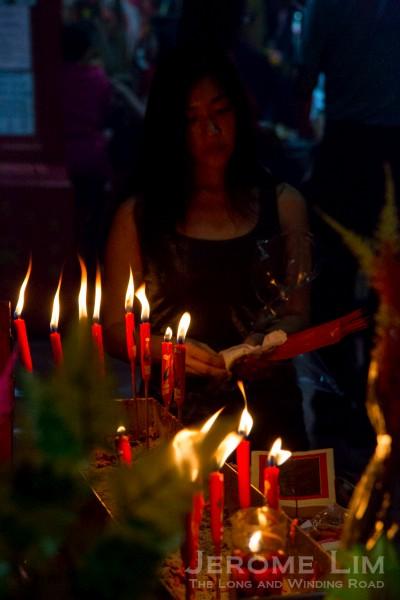 Lighting joss sticks at the temple.