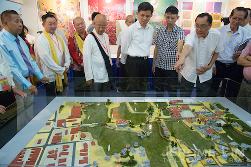 Minister, Prime Minister's Office, Chan Chun Sing - a former resident of the area, being shown a model of the Sar Kong village area at the exhibition.