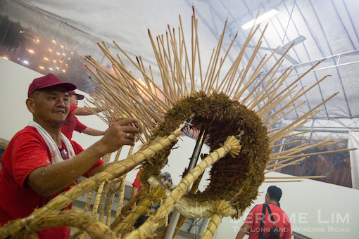 Lit joss sticks being placed on the straw dragon's body prior to the dance.