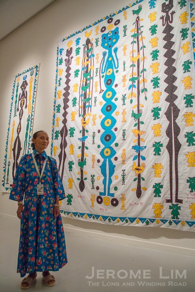 The dreams of a Shaman's wife. Tcheu Siong, a Hmong shaman's wife has her dreams reinterpreted as 'story' clothes in which one finds the spirits she sees in her dreams, represented by the lanky figures alongside representations of mountains, humans and animals.